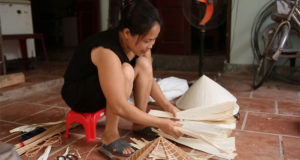 A laidy is working at Chuong conical hat village